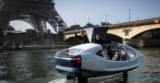 "TOPSHOT - Sea Bubbles start-up founders Alain Thebault (L) and Anders Bringdal (R) stand on board a Sea Bubble electric maritime ""flying taxi"" during a demonstration on May 20, 2018 on the river Seine in Paris, in front of the Eiffel Tower. - Aeronautical engineers and watermen Anders Bringdal and Alain Thebault are co-founders and developers of the Sea Bubbles zero-impact transportation ecosystem. (Photo by Lionel BONAVENTURE / AFP)        (Photo credit should read LIONEL BONAVENTURE/AFP/Getty Images)"